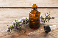 Essence of rosemary on wooden table Royalty Free Stock Images