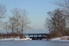 The essence of tranquility. Footbridge over stream emptying into Lake Ontario from Humber Bay Park East Stock Photography
