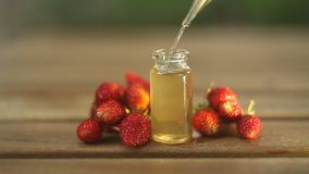 Essence of Wild strawberry on table in beautiful glass jar stock video footage