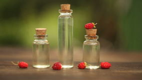Essence of wild strawberry on table in beautiful jar stock video footage