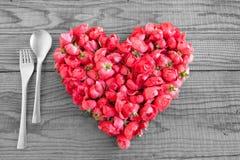 Essend in der Liebe, blüht ein Herz, das mit roten Rosen gemacht wird Lizenzfreies Stockbild