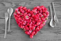 Essend in der Liebe, blüht ein Herz, das mit roten Rosen gemacht wird Stockfotos