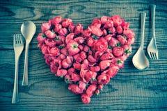 Essend in der Liebe, blüht ein Herz, das mit roten Rosen gemacht wird Lizenzfreie Stockbilder