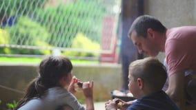 Essende Kinder und erwachsener Handelngrill stock footage