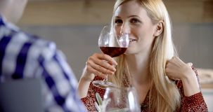 Essende, trinkende und sprechende Blondine Vier glückliche wirkliche offene Freunde genießen, das Mittagessen oder zu Abend zu es stock video