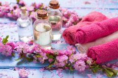 Essential aroma oil, flowers and towels   on blue wooden backgro Stock Image