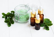 Essential aroma oil with massage salt and mint. On a white wooden table stock image