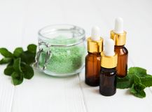 Essential aroma oil with massage salt and mint. On a white wooden table royalty free stock photography
