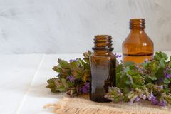 Essential aromatic oil with flowers on wooden background. Selective focus stock photos