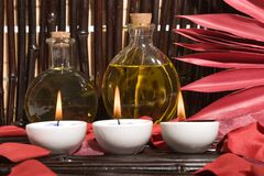Essential body massage oils with candles Royalty Free Stock Photography