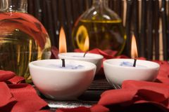 Essential body massage oils with candles Royalty Free Stock Image