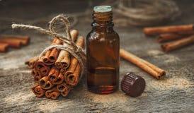 Essential cinnamon oil in a small bottle, ground cinnamon and ci Stock Photo
