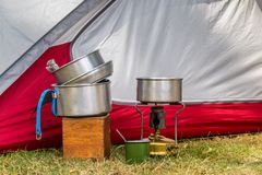 Cooking equipment on a campsite. Essential cooking equipment in front of a colorful tent on a campsite stock photos