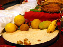 Essential Food. A plate with fruits like banana, orange, sweetlime, rice and a coconut in the background make essential food items for a hindu ritual Stock Photos