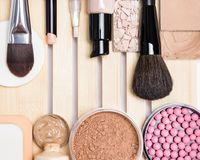 Essential make-up products to create the perfect complexion. Top view. Primer, concealer, foundation, cosmetic powder, blusher with makeup brushes and sponges royalty free stock photography