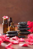 Essential oil azalea flowers black massage stones Stock Photos