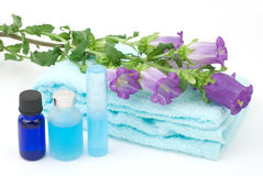 Essential oil and blue towel. With Campanula medium on white background Royalty Free Stock Image