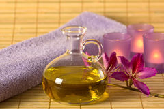 Essential oil, candles and purple towel. Stock Photo