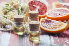 Essential oil citrus  with orange slices,  in glass bottle on ol Stock Photos