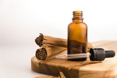Essential Oil Dropper and Glass Bottle With Cinnamon Stick II. An orange glass bottle with a dropper sitting next to cinnamon sticks Royalty Free Stock Photos