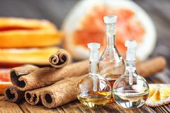 Essential oil in glass bottle with cinnamon sticks and dried red circle slices of citrus fruits orange and lemons on wooden backgr. Ound. Beauty treatment. Spa Royalty Free Stock Image