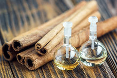 Essential oil in glass bottle with cinnamon sticks on wooden background. Beauty treatment. Spa concept. Selective focus. Stock Images