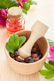 Essential oil in glass bottle, dried rose-hip berries and rose h Stock Images