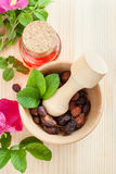 Essential oil in glass bottle, dried rose-hip berries in wooden Stock Images