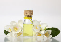 Essential Oil. Glass bottle with essential oil and flowers on a white background Royalty Free Stock Photo