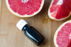 Essential oil in glass bottle with fresh, juicy grapefruit. Spa concept. Selective focus Stock Photos