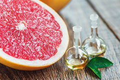 Essential oil with grapefruit. Essential oil in glass bottle with fresh, juicy grapefruit and green leaves-beauty treatment. Spa concept. Selective focus Royalty Free Stock Image