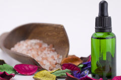 Essential oil. Green bottle of essential oil, potpourri and sea salt in wooden scoop Stock Images