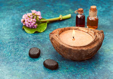 Essential oil, massage stones, flowers and candle Royalty Free Stock Photo