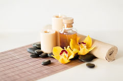 Essential oil, massage stones and orchid flower Stock Photos