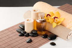 Essential oil, massage stones and orchid flower. Spa, health and beauty concept - closeup of essential oil, massage stones, candles and orchid flower stock images