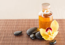 Essential oil, massage stones and orchid flower. Spa, health and beauty concept - closeup of essential oil, massage stones and orchid flower royalty free stock image