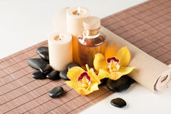 Essential oil, massage stones and orchid flower Royalty Free Stock Images