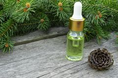 Essential oil of pine in a glass bottle with coniferous pine leaves on a table royalty free stock images