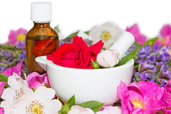 Essential oil and rose blossoms in mortar Royalty Free Stock Images