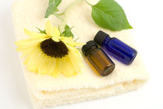 Essential oil on the yellow towel. With sunflower on white background Royalty Free Stock Images