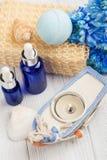 Essential oils, bath bomb, sponge, blue flowers Stock Photos