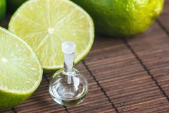 Essential oils in glass bottle with fresh, juicy, ripe limes. Beauty treatment. Spa concept. Selective focus. Small bottles of per. Fume stock images