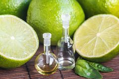 Essential oils in glass bottle with fresh, juicy, ripe limes. Beauty treatment. Spa concept. Selective focus. Small bottles of per. Fume stock photography