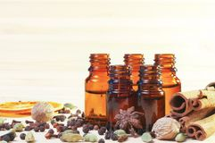 Essential oils in glass bottles and spices on wooden background with copyspace. Essential oils in glass bottles and spices - anise, nutmeg, cardamon, cinnamon Stock Images