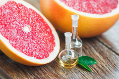 Essential oils with grapefruit. Essential oil in glass bottle with fresh, juicy grapefruit and green leaves-beauty treatment. Spa concept. Selective focus Stock Images