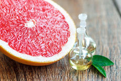 Essential oils with grapefruit. Essential oil in glass bottle with fresh, juicy grapefruit and green leaves-beauty treatment. Spa concept. Selective focus Royalty Free Stock Image