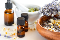 Essential oils with herbs. Alternative medicine with essential oils and herbs in white background Stock Images