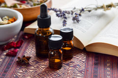 Essential oils with herbs and book. Alternative medicine with essential oils,herbs,and book royalty free stock image