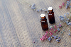 Essential oils and herbs on wooden background. Essential oil bottles and herbs on wooden background Stock Photo