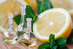 Essential oils. Essential oil in glass bottle with fresh, juicy lemon fruit and green leaves of mint-beauty treatment. Spa concept. Selective focus Royalty Free Stock Image